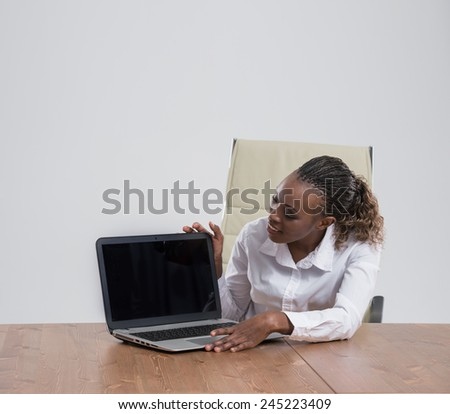 Excited female executive displaying laptop with a blank screen