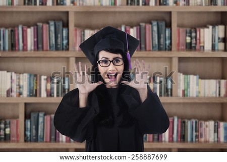 Excited female grad shouting happily in the library - stock photo