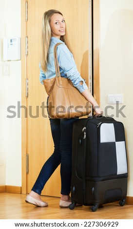 Excited female student with baggage ready to leave town for weekend