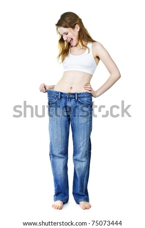 Excited fit young woman in loose old jeans after losing weight isolated on white - stock photo