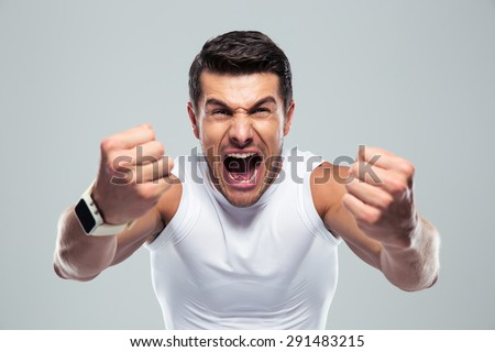 Excited fitness man shouting at camera over gray background - stock photo