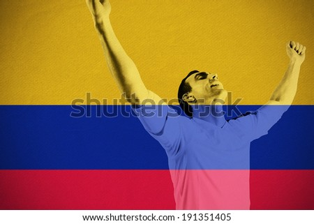 Excited football fan cheering against colombia national flag - stock photo