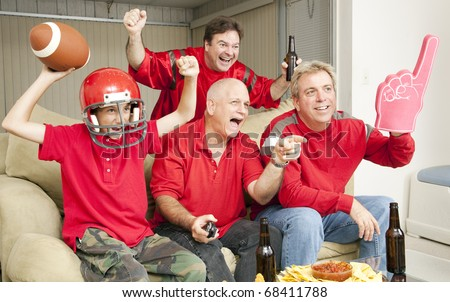 Excited football fans watching their team score a touchdown. - stock photo
