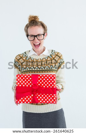 Excited geeky hipster holding present on white background - stock photo