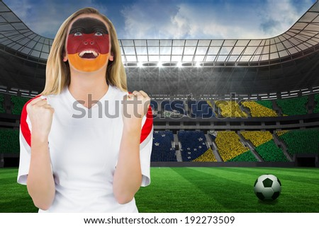 Excited german fan in face paint cheering against large football stadium with brasilian fans - stock photo