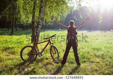 Excited girl cyclist standing in a spring park with hands outstretched. Sunny outdoor - stock photo