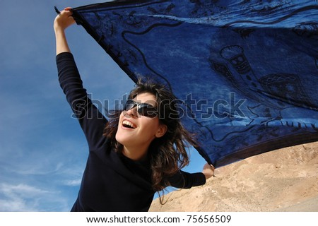 Excited girl dancing with a blue shawl on a windy day. - stock photo