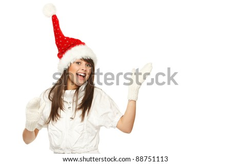Excited girl in Santa hat showing empty copy space, over white background - stock photo