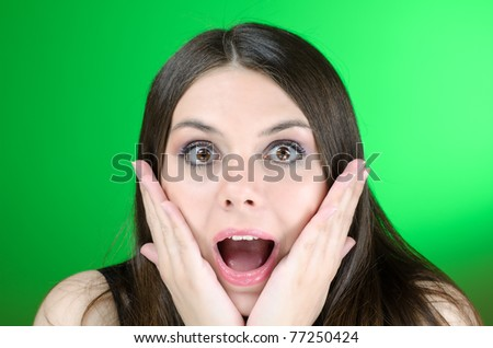 Excited girl on green background - stock photo