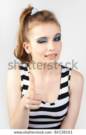 Excited girl pointing at you with a naughty winks againt. Success woman showing thumbs up and woman pointing her finger. - stock photo