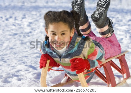 Excited girl sledding down snowy hill on sled - stock photo