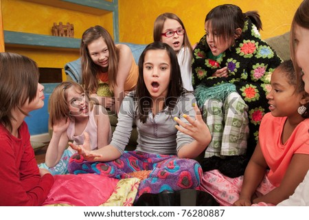 Excited girl talking with her friends at a sleepover - stock photo