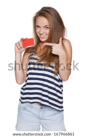 Excited girl teenager hipster holding pointing to the blank credit card, over white background - stock photo