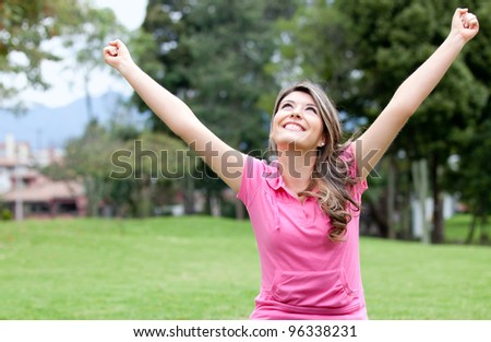 Excited girl with arms up and smiling at the park - stock photo
