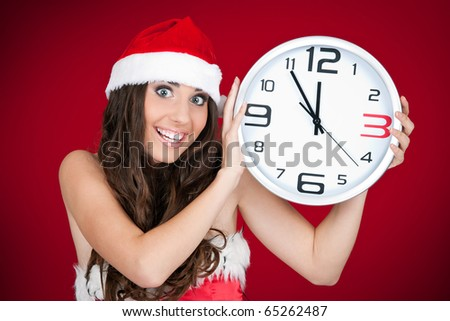 excited girl with sanat hat  holding a clock and pointing at time - stock photo