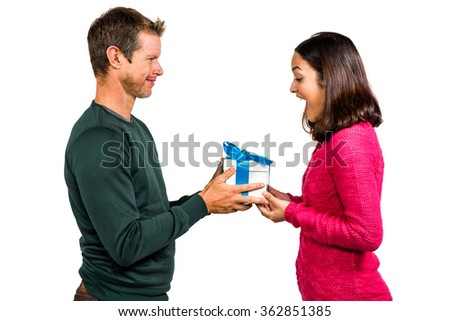 Excited girlfriend taking gift from boyfriend against white background - stock photo