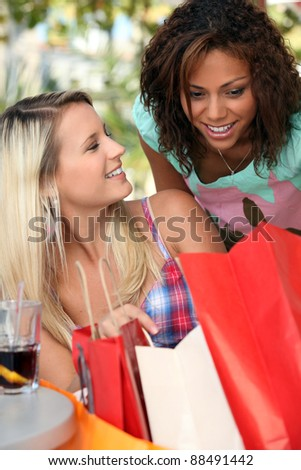 Excited girls watching their shopping bags - stock photo