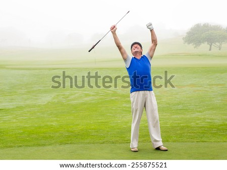 Excited golfer cheering on putting green on a foggy day at the golf course - stock photo