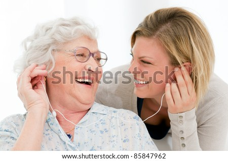Excited grandmother listening music together with her granddaughter at home - stock photo