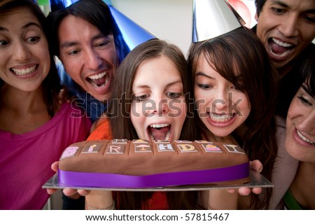 Excited group of friends smiling and biting a birthday cake
