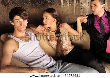 Excited group of people at nightclub sitting on sofa - stock photo