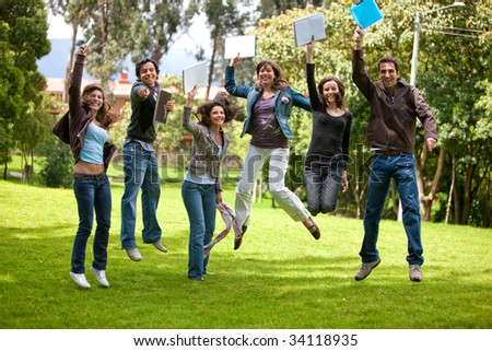 Excited group of students jumping outdoors with notebooks