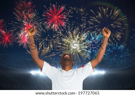 Excited handsome football fan cheering against fireworks exploding over football stadium