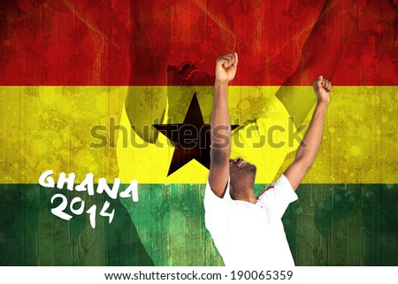 Excited handsome football fan cheering against ghana flag in grunge effect - stock photo