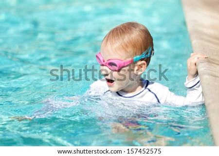 excited happy boy in the swimming pool having fun