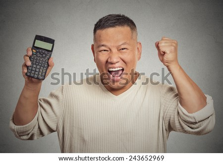 Excited happy business man person showing calculator with million number sign on screen isolated on grey wall office background. Human face expression emotion feeling. Economy financial wealth concept - stock photo