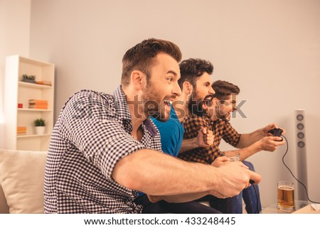 excited happy cheerful man play video game with his friends - stock photo