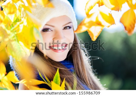 Excited happy fall woman smiling joyful and blissful holding autumn leaves outside in colorful fall forest - stock photo