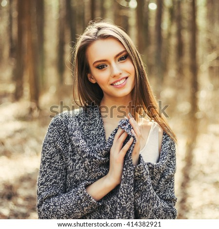 Excited happy fall woman smiling joyful and blissful holding autumn leaves outside in colorful fall forest.  - stock photo