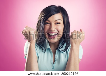 Excited, happy girl with fists up showing success, isolated on pink background. - stock photo