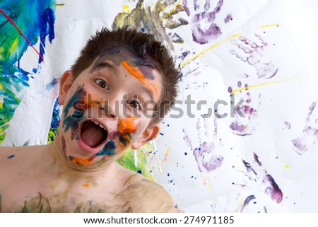 Excited happy little boy doing finger painting standing laughing at the camera with a wide open mouth in front of his artwork with vibrant colors and hand prints - stock photo