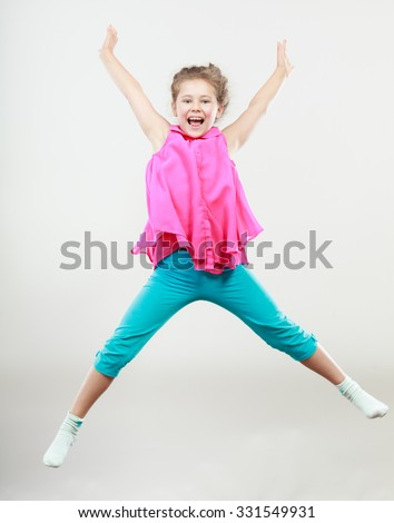 Excited happy little girl jumping for joy in air. Joyful cheerful kid in studio with arms raised up. - stock photo
