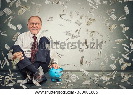Excited happy senior man sitting on a floor with piggy bank under a money rain isolated on gray wall background. Positive emotions financial success luck good economy concept