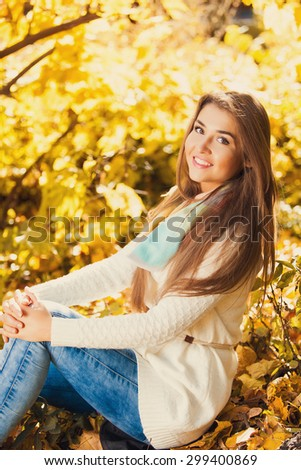 Excited happy woman smiling joyful and blissful holding autumn leaves outside in colorful fall forest.