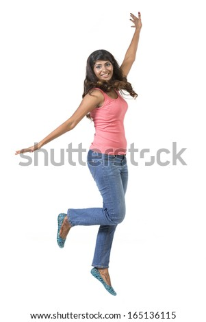 Excited Indian woman jumping for joy. Beautiful Asian woman jumping isolated on white background. - stock photo