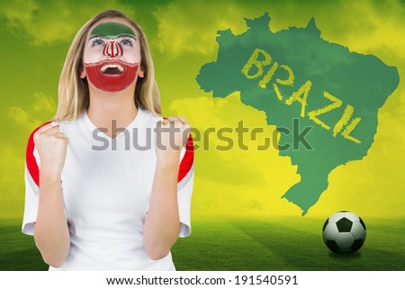 Excited iran fan in face paint cheering against football pitch with brazil outline and text - stock photo