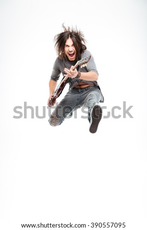 Excited joyful young male guitarist with electric guitar shouting and jumping over white background - stock photo