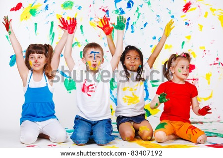 Excited junior students with hands painted - stock photo