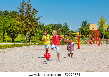 Excited kids running with a ball on the playground - stock photo