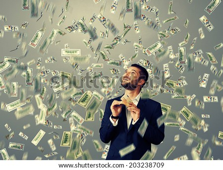 excited laughing businessman standing under dollar's rain, holding money and looking up  - stock photo
