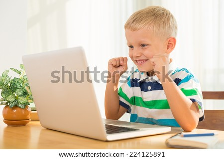 Excited little boy looking at the laptop screen - stock photo
