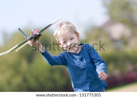 excited little boy running with a toy plane - stock photo