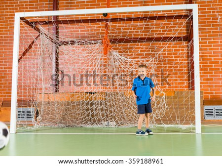 Excited little boy standing in the goalposts on an indoors soccer court as he waits expectantly for a player to take a shot at goal