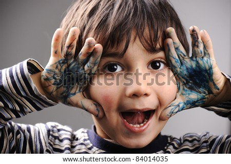 Excited little boy with messy color hands - stock photo