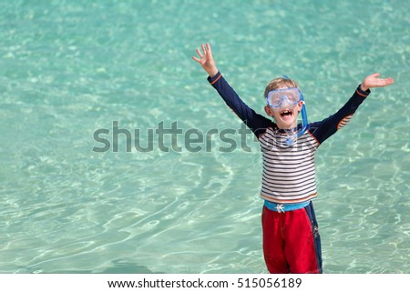 excited little boy with snorkeling gear holding his hands up and laughing at the beach, vacation and emotion concept