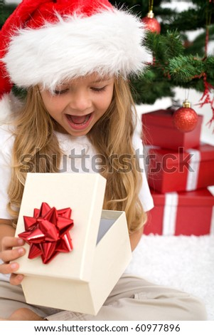 Excited little girl opening christmas present in front of the fir tree - closeup - stock photo